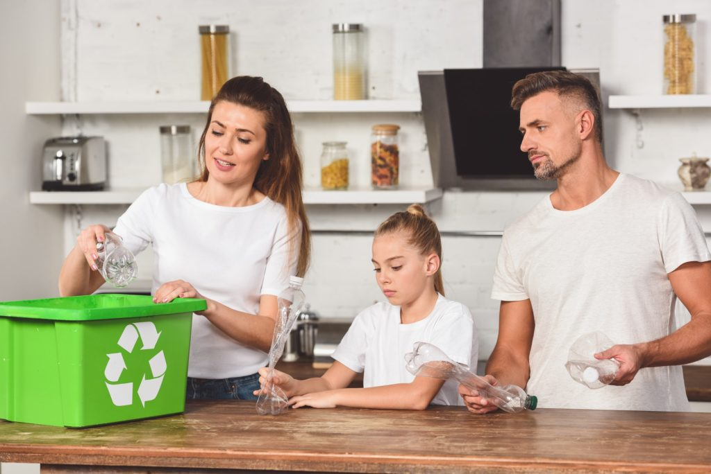 family standing at kitchen and putting empty plastic bottles in recycle box