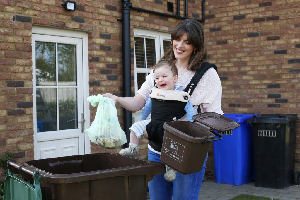 Mother putting food waste in brown bin