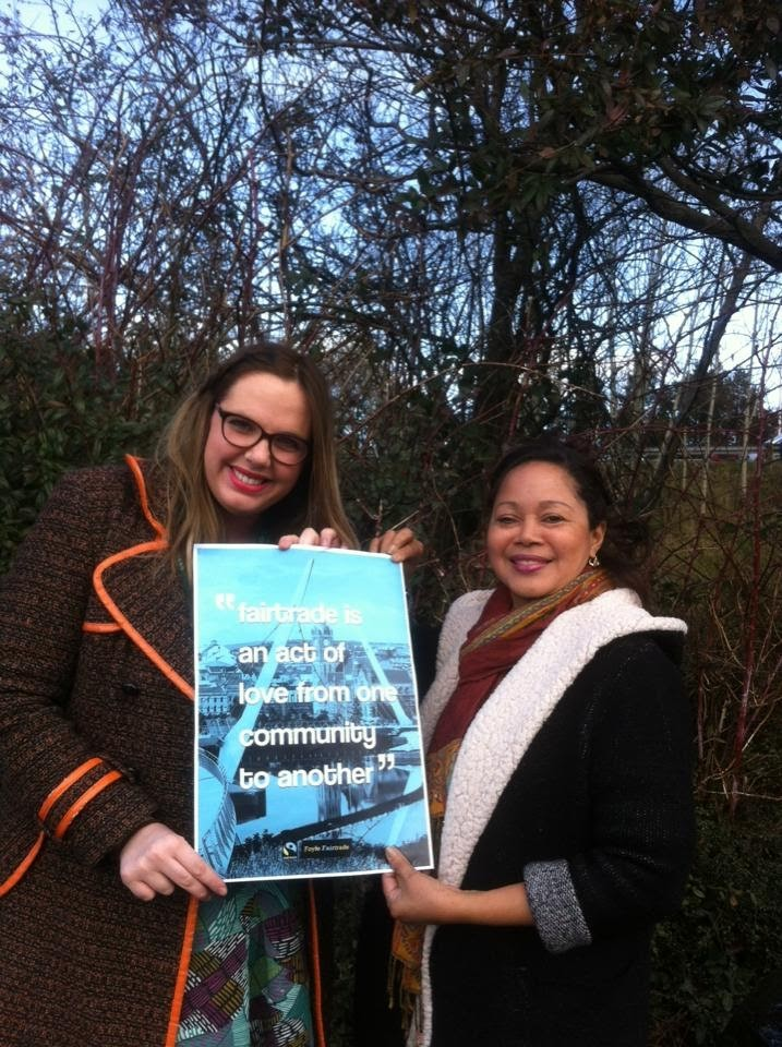Donna McFeely presents the 'Fairtrade is an act of love' poster to visiting Fairtrade banana farmer Maria Genao from Dominican Republic.